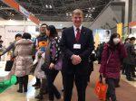 統合医療展のセミナーであふれる人だかりを避けて撮影に応じるUBMジャパンのクリストファー・イブ社長
